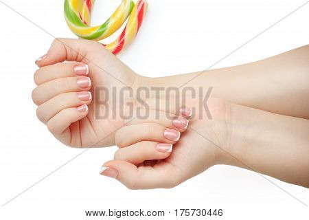 Beautiful woman's nails with beautiful french manicure isolated in white background with candy