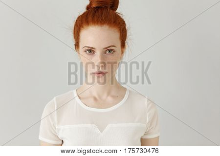 Indoor Portrait Of Attractive Good-looking Redhead Girl With Hair Bun And Freckles Having Serious Fa