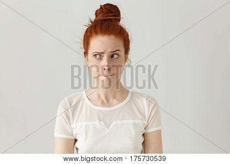 Indoor Shot Of Cute Redhead Girl Looking Away, Having Doubtful And Indecisive Face Expression, Pursu
