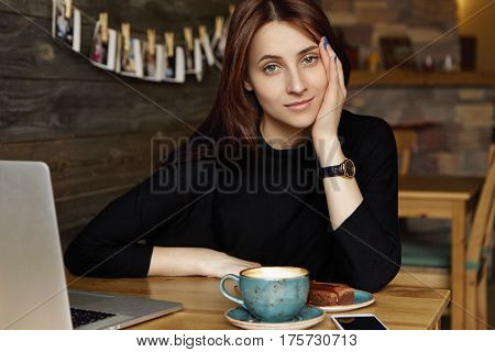 Portrait Of Bored Young Caucasian Woman In Black Clothing Leaning Face On Hand While Having Coffee A
