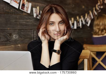 Indoor Shot Of Charming Young Female With Chocolate Hair Wearing Black Dress And Watch On Her Wrist,