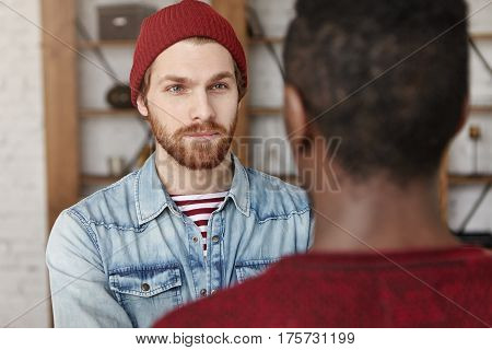Interracial Friendship Concept. Handsome Bearded European Hipster Wearing Hat And Denim Jacket Havin