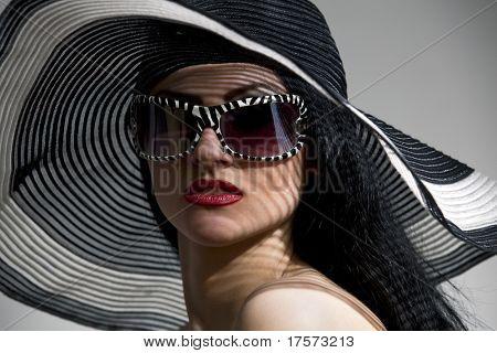 Vacker modell i randig hatt och topp med glasögon på den grå bakgrunden