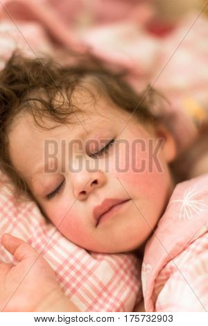 Cute toddler sleeping in her bed with pink bedding.