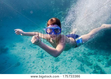 Boy in swimming mask deep dive in Red sea near coral reef, underwater shoot