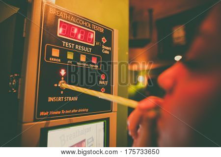 Close up shot of an alcohol tester on a wall and a person blowing through a straw.