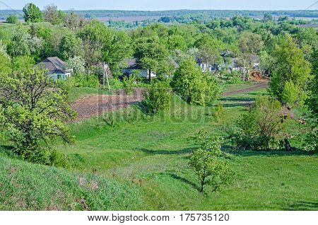 The outskirts of village located in the ravine riotously overgrown with vegetation in the period of plowing the land