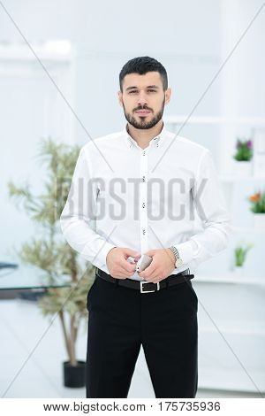 Handsome smiling confident businessman portrait in office