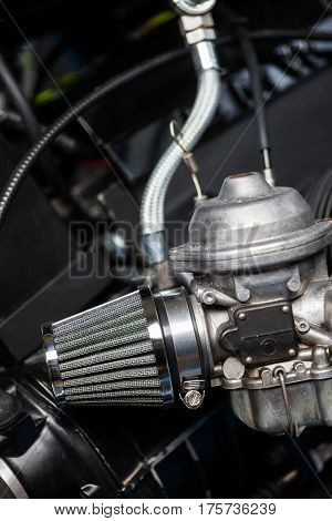 Close up shot of a motorcycle carburetor with air filter.