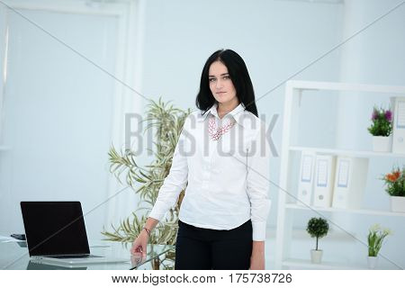 Businesswoman working in office lobby and using laptop computer.