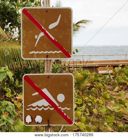 No words needed on a no swimming and no diving sign located at the ocean in Puerto Rico