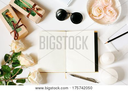 Opened empty diary, sunglasses, pen, vintage tray, candles, roses on white background. Flat Lay, top view, mockup