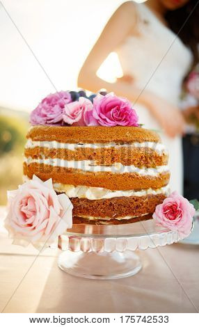 Homemade wedding naked cake decorated with flowers on glass cut stand