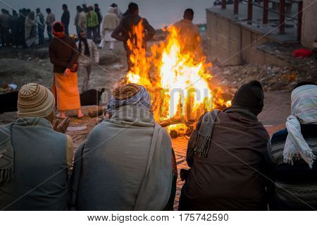 People look at the funeral pyre that night. The ceremony of the cremation of Manikarnika Ghat on the banks of the Ganges river in Varanasi India.