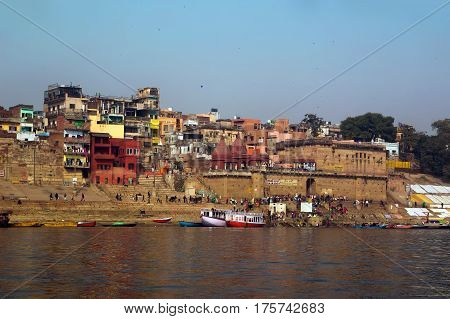 the view from the boat to the shore of the sacred river Ganges in Varanasi. Holiday a lot of people on the river Bank.