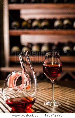 Wine vault location. Wine carafe and wine glass placed on a wooden table