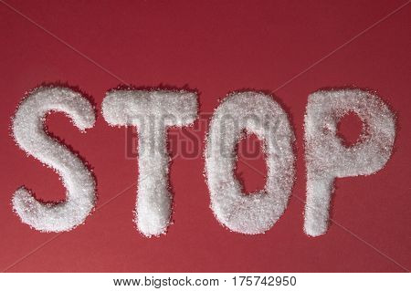 The word STOP written by sugar grains on red background. Top view