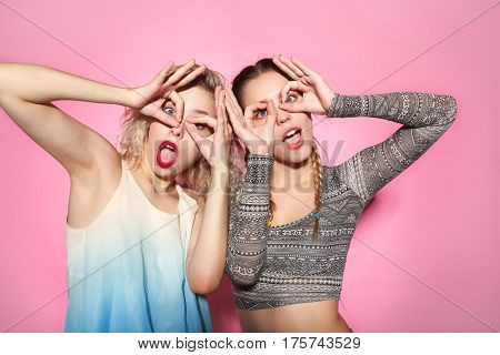 Pretty young women making faces on camera and gesturing goggles with hands. Horizontal studio shot.