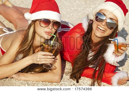 Two young beautiful women in christmas suit with martini glass on the beachfront