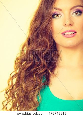 Fashion hairstyle beauty concept. Portrait of young attractive woman with curly brown hair wearing colorful makeup and blue top indoor shot on yellow background