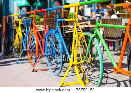 Creative metal fence of painted frames of old bicycles. Fashion design European modern Scandinavian street. Food area a bright Sunny day. Helsinki Finland Suomi