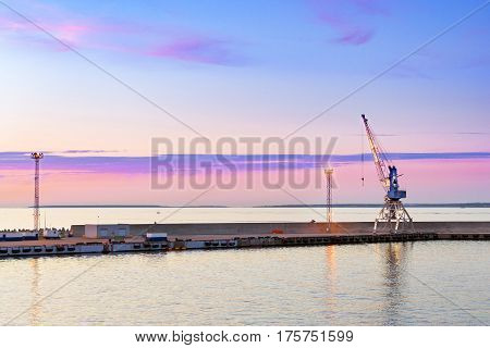 Multi-ton industrial port crane on rails lifts heavy loads in marine passenger-cargo harbour of Tallinn. Evening panorama of sea bay at sunset. Concrete seawall with lighting masts & crane. Estonia