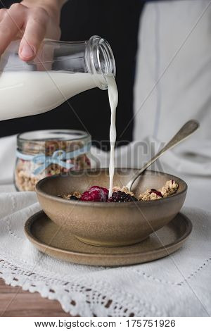 Milk is pouring to brown bowl with cereal.