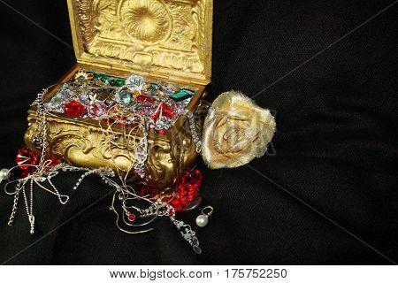 Golden treasure chest box with jewelry gems on dark background