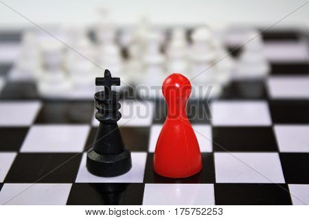 Black king and red lady queen figurine of ludo and white blurry chess pieces in the distance. On chess board interesting concept.