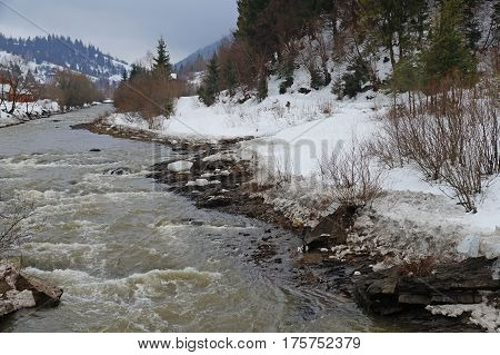 The mountain river flows violently between the snow-capped mountains.