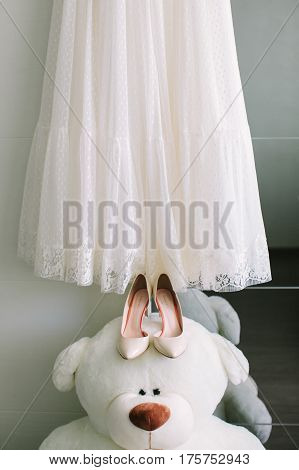 charges of the bride: the beautiful lacy white wedding dress and elegant shoes lying on a big white teddy bear.