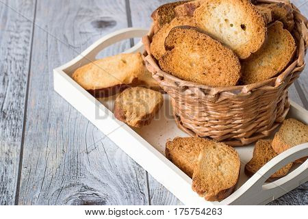 Basket with homemade rusks on a white tray on a gray wooden table.