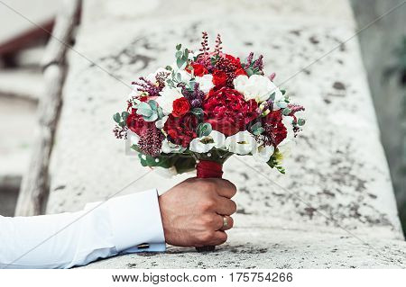 luxurious wedding bouquet with red ribbon made of red and white roses and peony in a hand of fiance on a stone