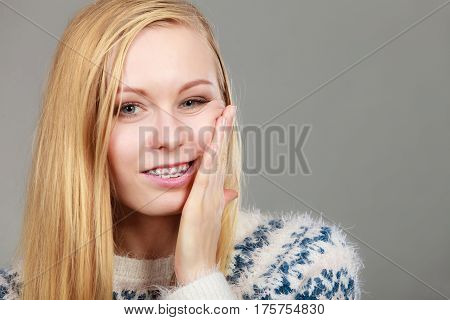 Adolescence teenage problems concept. Young teenager blonde girl thinking with hand on her cheek.