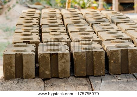 Raw bricks covered with sawdust drying in the open air. poster