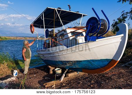 PELOPONNESE, GREECE - JULY 9, 2016: A fisherman paints his traditional wooden boat on July 9, 2016 in Peloponnese, Greece. Fishing in wooden traditional boats remains an important part of the local economy in Greece.