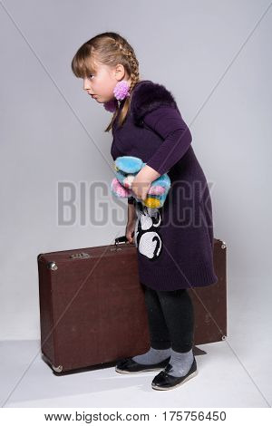 Teenage girl with a large old suitcase and a plush toy in her hand
