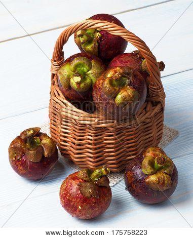 Arrangement of Fresh Ripe Mangosteen in Wicker Basket closeup on Light Wooden background