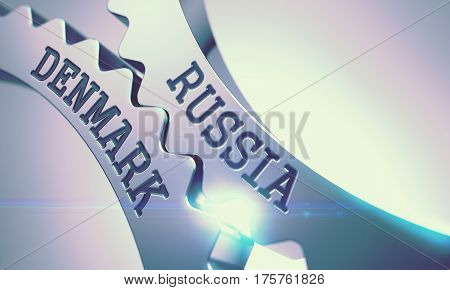 Russia Denmark on the Mechanism of Shiny Metal Cog Gears with Lens Effect - Interaction Concept. Shiny Metal Cog Gears with Russia Denmark Inscription. 3D.