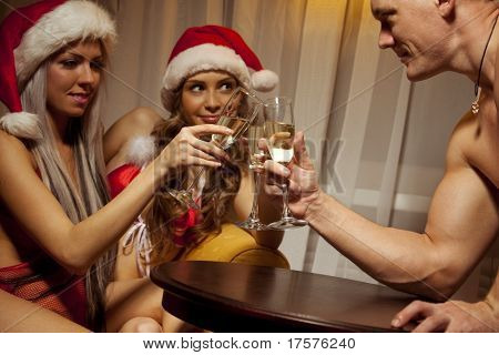 Portrait of two sexy girls in Santa hats holding the glasses of champagne and clinking glasses with handsome man (Focus is on champagne glasses)