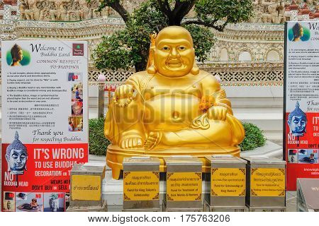 Bangkok, Thailand - January 9, 2016: Gold Hotey statue is set for people to worship in Wat Arun, Bangkok, Thailand. Boxes requesting donations and rules of conduct in the temple written on the stands