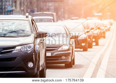 Close-up of the lane congested with lots of cars against the warm sunlight