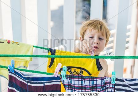 A Little Boy Helps Her Mother To Hang Up Clothes