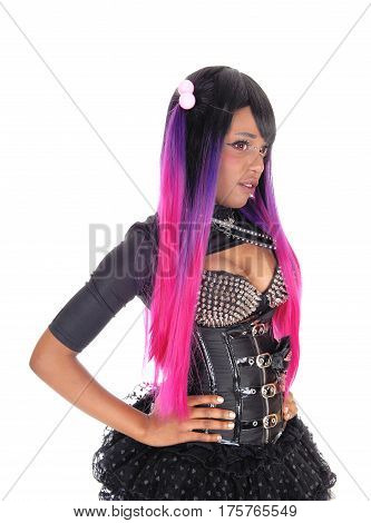 A beautiful African American steampunk woman ins corset and spike bra standing in short skirt in profile isolated for white background.