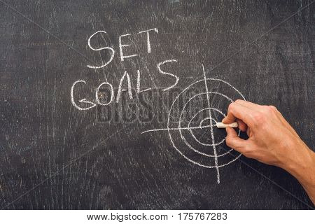 Hand Writing Set Goals Topic On Chalkboard