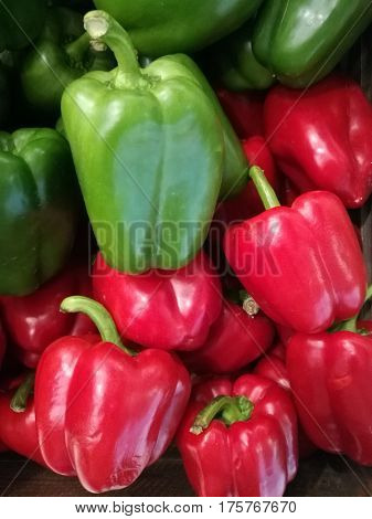 Fresh organic bell green and red pepper stand out among many pepper background in wood tray in supermarket. Heap of bell red and green pepper Close-up