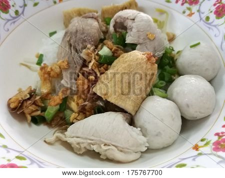 Hearty eating meal noodle with fish ball fishcake slices and boiled pork for light breakfast or lunch focus on foreground with blur background Fish ball noodle bowl in restaurant