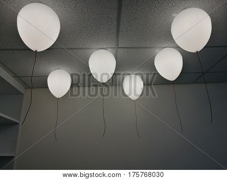 LED white creamy balloons burning fly away in the sky at night in the office room with blur white wall background holiday celebration decoration