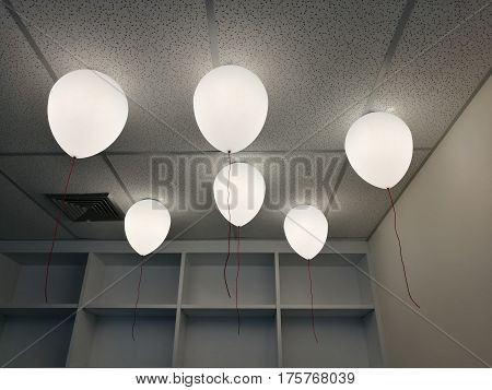 LED white creamy balloons burning fly away in the sky at night in the office room with blur white wood shelf background holiday celebration decoration