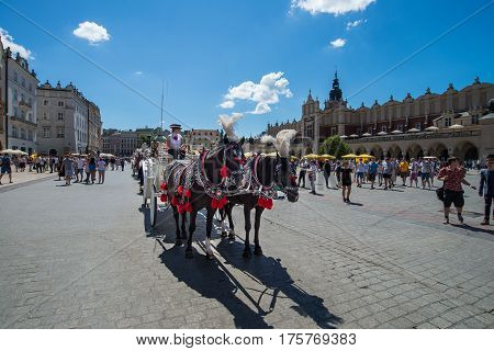KRAKOW - JUNE 18: Horse carriages at the main square in Krakow on June 18. 2016 in Poland